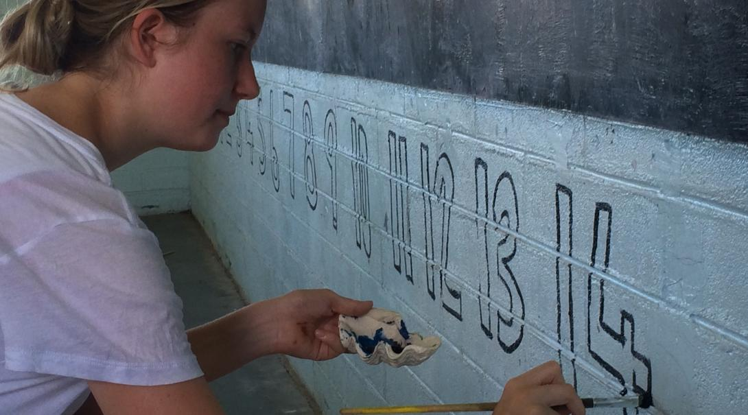 An Alternative Schoolies volunteers paints a mural of numbers on a classroom wall in Samoa.